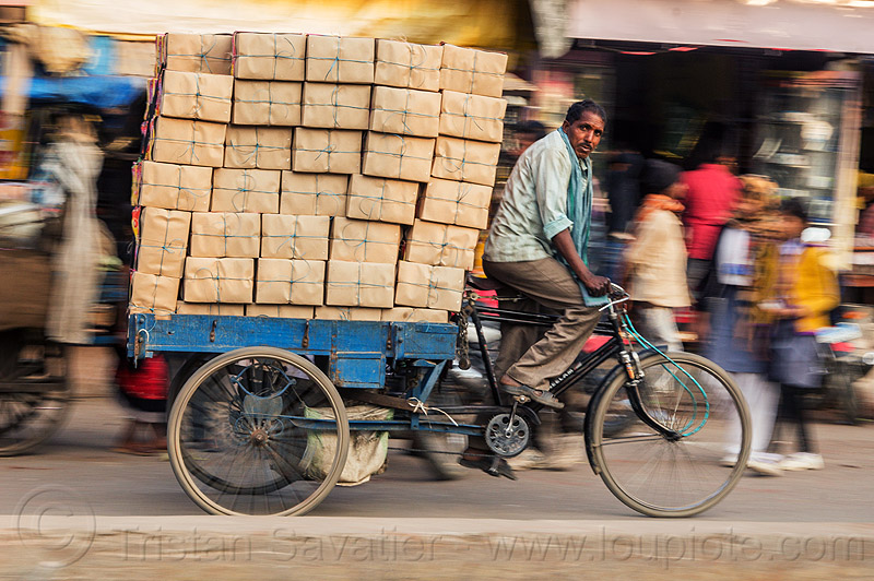 man with load of boxes on cargo tricycle (india), bearer, boxes, cargo tricycle, cargo trike, cycle rickshaw, freight tricycle, freight trike, heavy, india, load, man, moving, riding, transport, transportation, transporting, varanasi