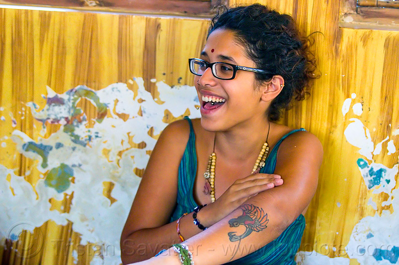 maryam and peeling paint wall, arm tattoo, bindi, bird tattoo, bracelets, djembe drum, drummer, eyeglasses, eyewear, maryam, musical instrument, necklaces, peeling paint, percussion, phoenix tattoo, prescription glasses, rishikesh, sitting, spectacles, tattoos, tongue piercing, wall, woman