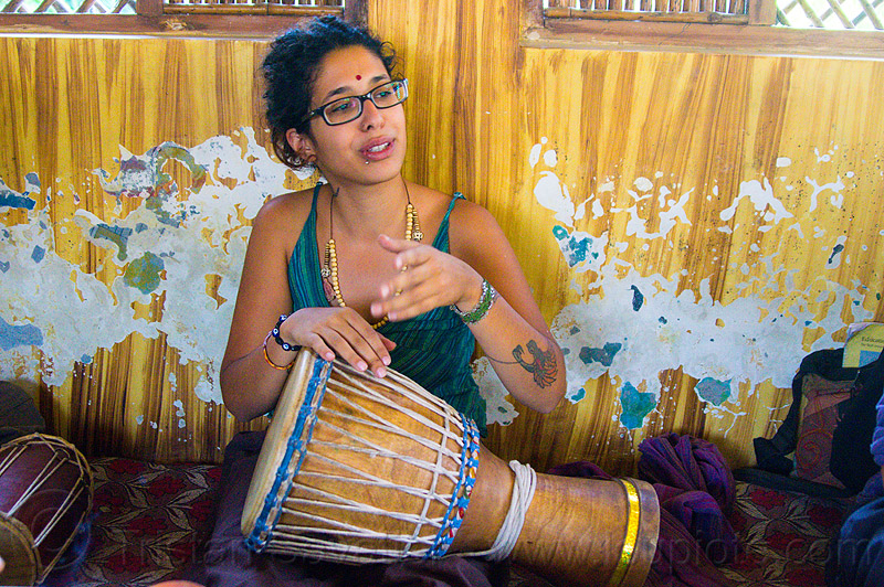 maryam with djembe drum, arm tattoo, bindi, bird tattoo, bracelets, djembe drum, drummer, eyeglasses, eyewear, maryam, musical instrument, necklaces, peeling paint, percussion, phoenix tattoo, prescription glasses, rishikesh, sitting, spectacles, tattoos, wall, woman