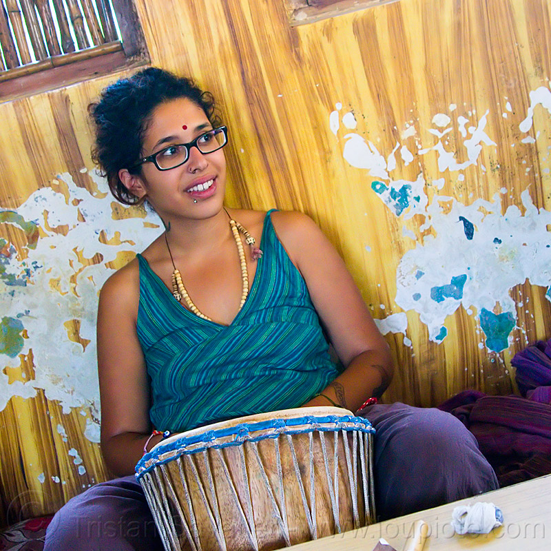 maryam with djembe drum, bindi, bracelets, djembe drum, drummer, eyeglasses, eyewear, lip piercing, maryam, musical instrument, necklaces, peeling paint, percussion, prescription glasses, rishikesh, sitting, spectacles, wall, woman