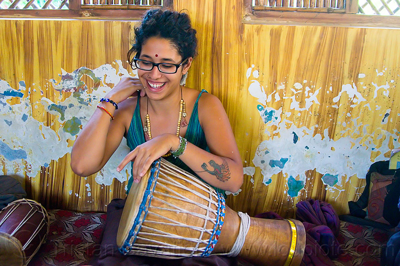 maryam with djembe drum, arm tattoo, bird tattoo, bracelets, drummer, eyeglasses, eyewear, musical instrument, necklaces, peeling paint, people, percussion, phoenix tattoo, prescription glasses, rishikesh, sitting, spectacles, tattoos, tilaka, wall, woman