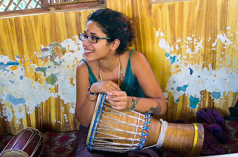 maryam with djembe drum, arm tattoo, bindi, bird tattoo, bracelets, djembe drum, drummer, eyeglasses, eyewear, india, maryam, musical instrument, necklaces, peeling paint, percussion, phoenix tattoo, prescription glasses, rishikesh, sitting, spectacles, tattoos, woman
