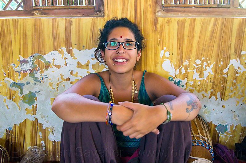 maryam with djembe drum, bracelets, drummer, eyeglasses, eyewear, lip piercing, musical instrument, necklaces, peeling paint, people, percussion, prescription glasses, rishikesh, sitting, spectacles, tilaka, wall, woman