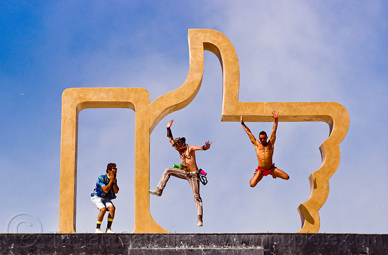 men jumping in the giant golden hand - burning man 2013, art, art installation, dadara, facebook, facebook hand, facebook like, golden like, icon, jumpshop, like4real, people, sculpture, thumb up