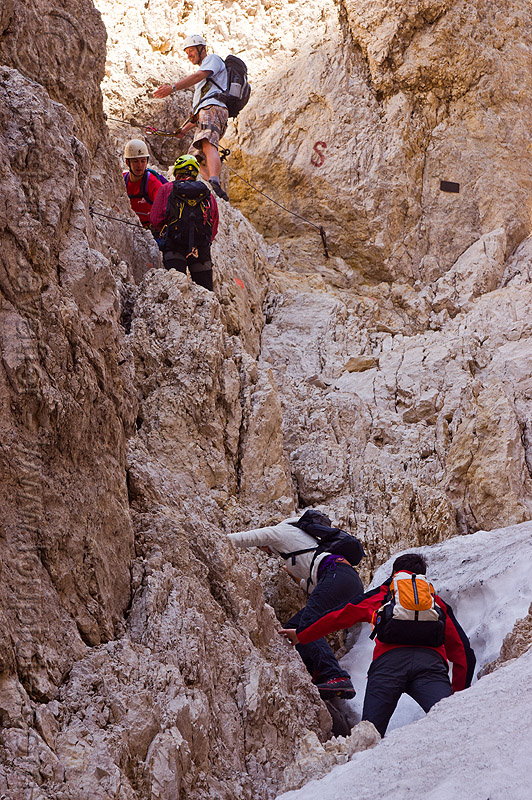 montaineers ascending the santner pass via ferrata in the dolomites, alps, climbers, climbing helmet, dolomites, dolomiti, ferrata santner, mountain climbing, mountaineer, mountaineering, mountains, old snow, rock climbing, via ferrata del passo santner