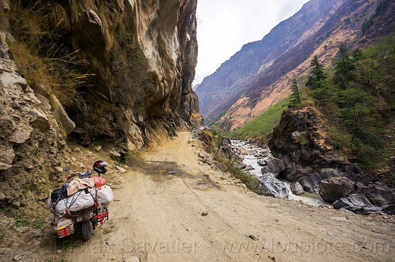 motorbike on road between tatopani and jomsom (nepal), annapurnas, bags, cliff, dirt road, kali gandaki river, kali gandaki valley, luggage, motorcycle touring, mountain road, mountains, sacks, stream, unpaved