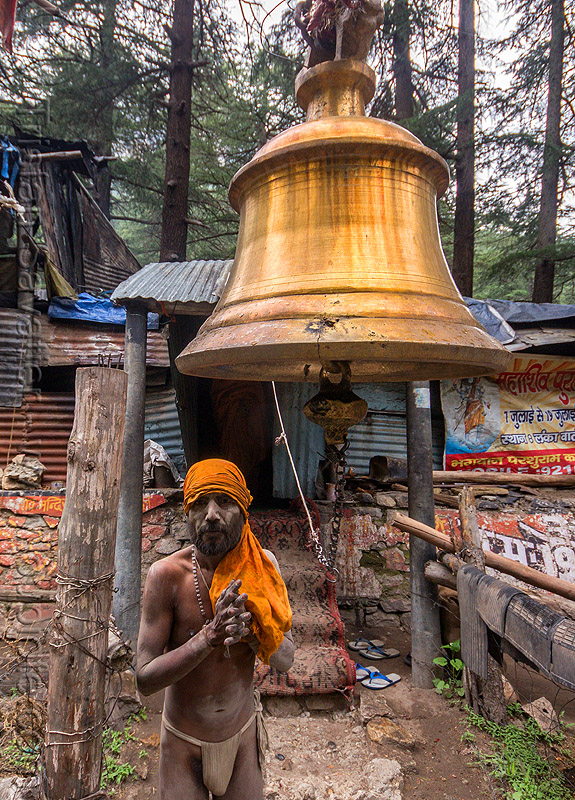 naga baba under large bell on the road to gangotri (india), bhagirathi valley, brass, hinduism, holy ash, man, naga sadhu, naked, people, sacred ash, saffron color, standing, vibhuti