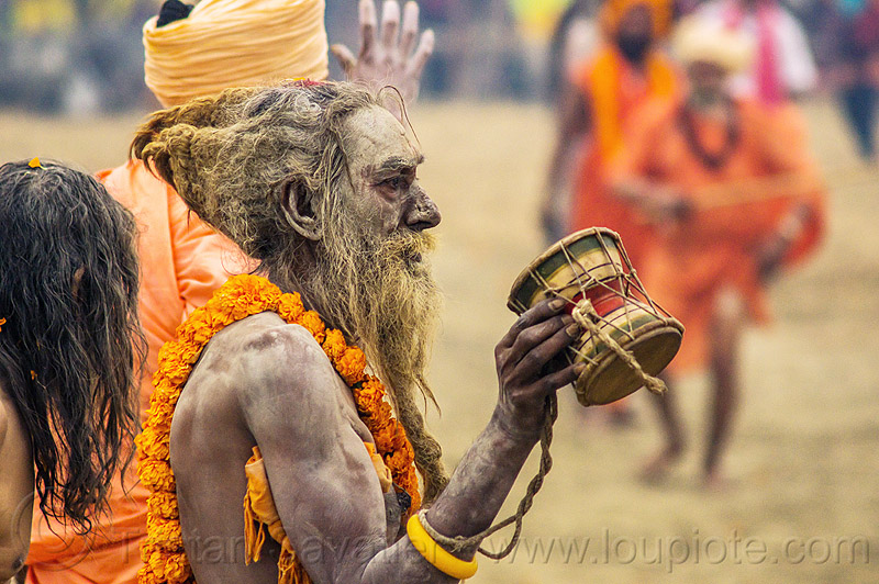 naga sadhu (hindu devotee) with ritual drum - kumbh mela hindu festival (india), beard, damaru drum, dreadlocks, dreads, flower necklace, hindu, hinduism, holy ash, kumbha mela, maha kumbh mela, marigold flowers, men, naga babas, naga sadhus, naked, orange flowers, procession, ritual drum, sacred ash, sadhu, vasant panchami snan, vibhuti, walking