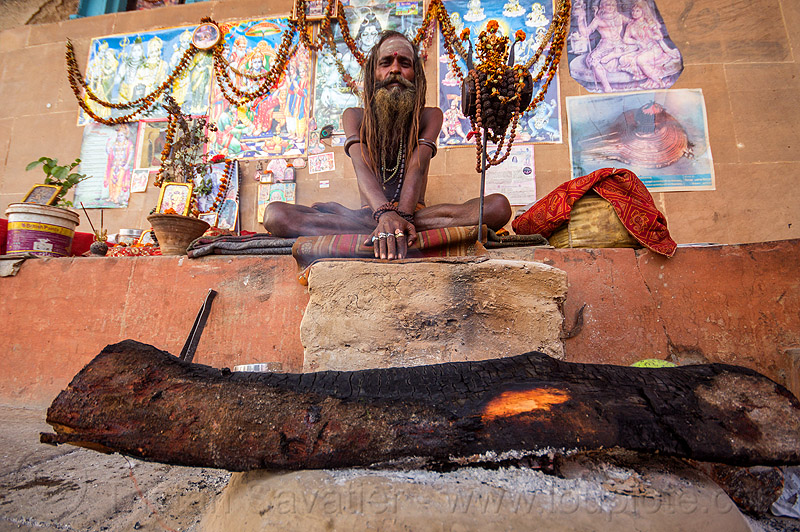 naga sadhu (india), baba, beard, campfire, damaru drum, dreads, ghats, hindu, hinduism, man, posters, ritual drum, sadhu, sitting, tree log, varanasi, wall, wood