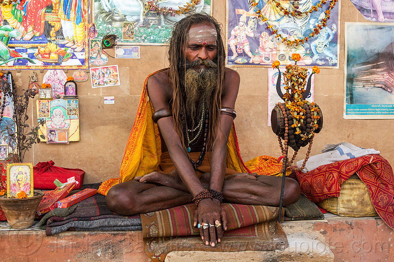naga sadhu (india), baba, beads, beard, bracelets, damaru drum, dreadlocks, dreads, finger rings, ghats, hindu, hinduism, man, necklaces, posters, ritual drum, sadhu, sitting, tilak, tilaka, trident, varanasi, wall
