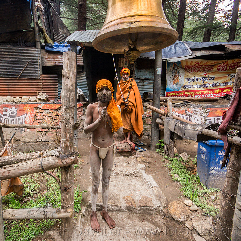 naga sadhu under large bell on gangotri road (india), baba, bell, bhagirathi valley, brass, hinduism, holy ash, men, naga babas, naga sadhus, naked, sacred ash, sadhu, saffron color, standing, vibhuti