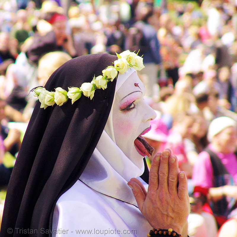 nun praying - the sisters of perpetual indulgence - easter sunday in dolores park, san francisco, crown, drag, flower crown, flowers, hands, hunky jesus contest, makeup, man, nuns, people, saint rita of cascia, sister mary timothy simplicity, sticking out tongue, sticking tongue out