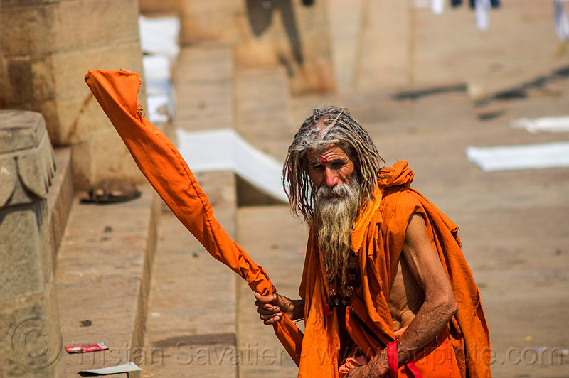 old hindu man in saffron color cloth on the ghats of varanasi (india), baba, beard, bhagwa, dreadlocks, dreads, ghats, hindu, hinduism, old man, pilgrim, sadhu, saffron color, staff, varanasi