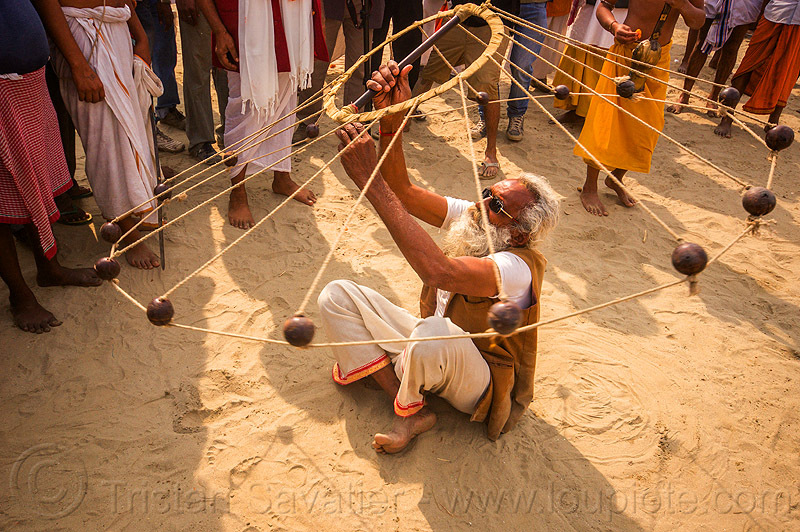 old man spinning balls with ropes (india), crowd, game, hindu pilgrimage, hinduism, india, indian spinning balls, maha kumbh mela, man, metal balls, performer, ropes, sitting, spectators, white beard