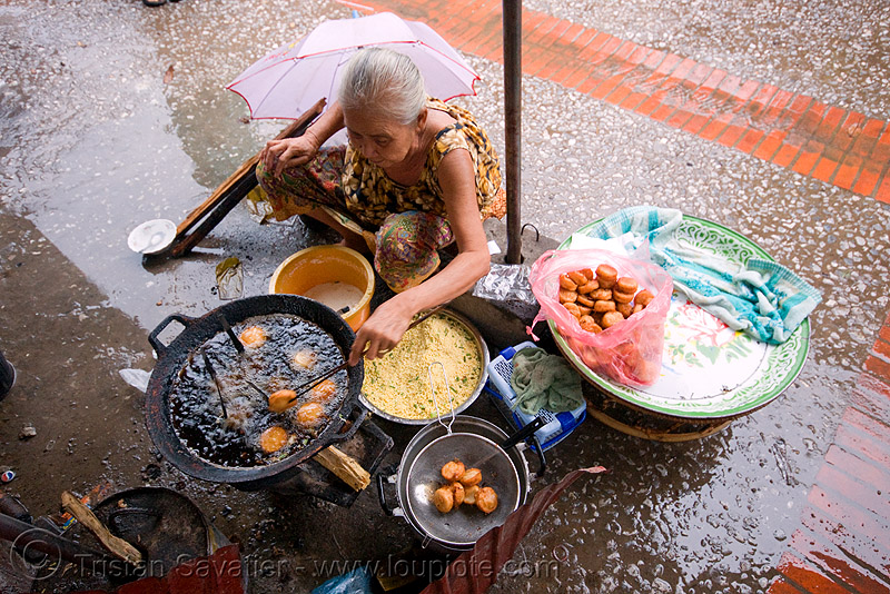 old woman cooking excellent little cakes in the market - luang prabang (laos), asian woman, cakes, cooking, deep frying, fire, frying oil, frying pan, laos, luang prabang, mature woman, old, street food, street market, street seller, street vendor, wok