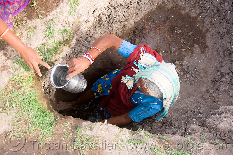 old woman getting drinking water from water hole - mandu (india), mandav, people