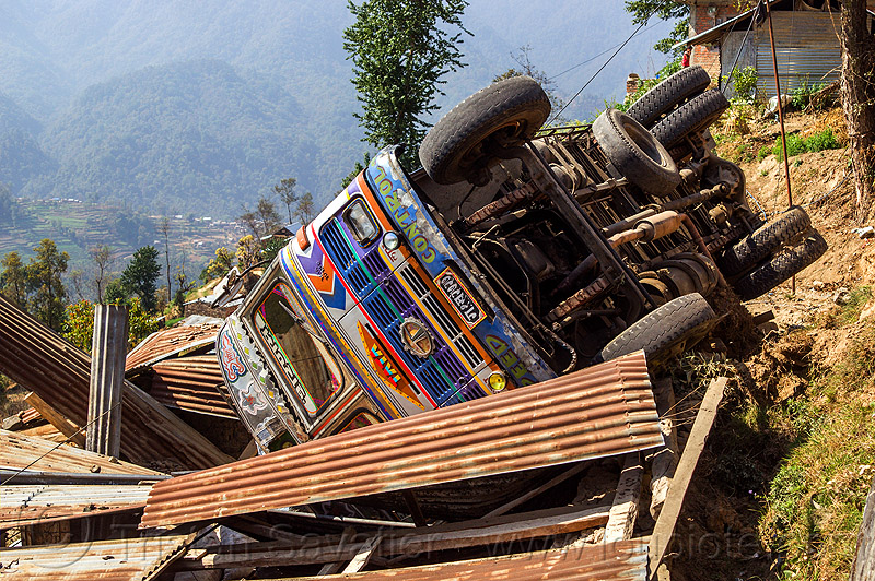 overturned truck crashed on house roof (nepal), accident, corrugated, corrugated metal, crash, ditch, lorry, mountain road, rollover, tata, tata motors, traffic accident, truck accident, up-side-down, wreck