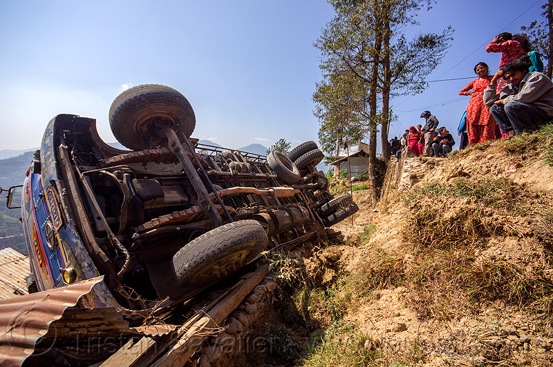 overturned truck lands on village house (nepal), crash, ditch, lorry, mountain road, overturned, rollover, tata motors, traffic accident, truck accident, underbelly, up-side-down, wreck