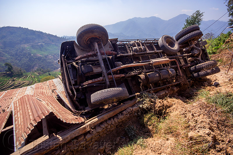 overturned truck on house roof (nepal), corrugated metal, crash, ditch, lorry, mountain road, overturned, rollover, tata motors, traffic accident, truck accident, underbelly, up-side-down, wreck