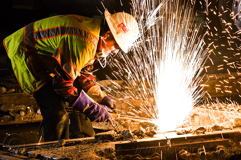 oxy-acetylene cutting torch, high-visibility jacket, high-visibility vest, light rail, man, muni, night, ntk, oxy-acetylene cutting torch, oxy-fuel cutting, railroad construction, railroad tracks, railway tracks, reflective jacket, reflective vest, safety glasses, safety gloves, safety helmet, safety vest, san francisco municipal railway, sparks, track maintenance, track work, welder, worker, working