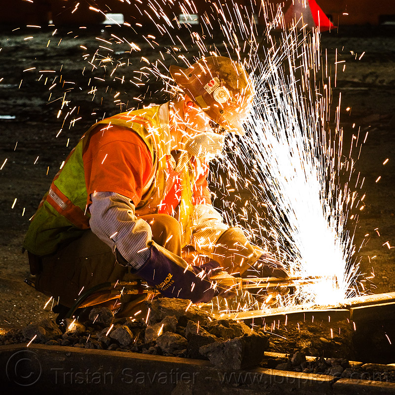 oxy-acetylene cutting torch, dust mask, high-visibility jacket, high-visibility vest, light rail, man, muni, night, ntk, oxy-acetylene cutting torch, oxy-fuel cutting, railroad construction, railroad tracks, rails, railway tracks, reflective jacket, reflective vest, safety glasses, safety helmet, safety vest, san francisco municipal railway, sparks, track maintenance, track work, welder, worker, working