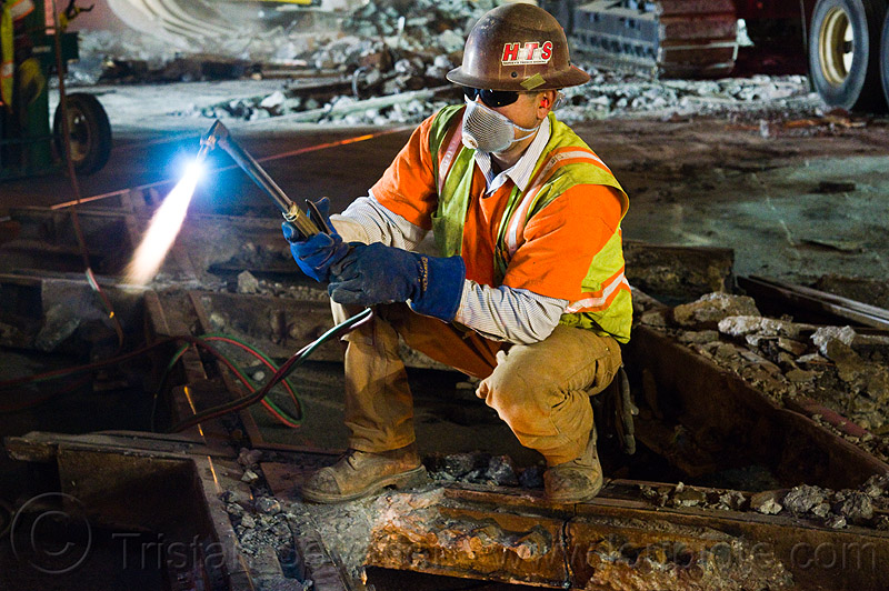 oxy-acetylene torch, blue flame, fire, flames, high-visibility jacket, high-visibility vest, light rail, man, muni, night, ntk, oxy-acetylene cutting torch, oxy-fuel cutting, railroad construction, railroad tracks, rails, railway tracks, reflective jacket, reflective vest, safety helmet, safety vest, san francisco municipal railway, track maintenance, track work, welder, worker, working