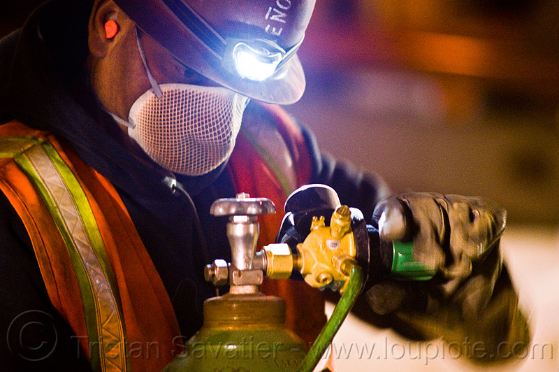 oxygen tank valve, dust mask, face-mask, gas tank, headlamp, headlight, high-visibility jacket, high-visibility vest, light rail, man, muni, night, ntk, oxy-acetylene, oxygen, pressure gauge, railroad construction, railroad tracks, railway tracks, reflective jacket, reflective vest, regulator, safety glasses, safety gloves, safety helmet, safety vest, san francisco municipal railway, track maintenance, track work, valve, welder, worker, working
