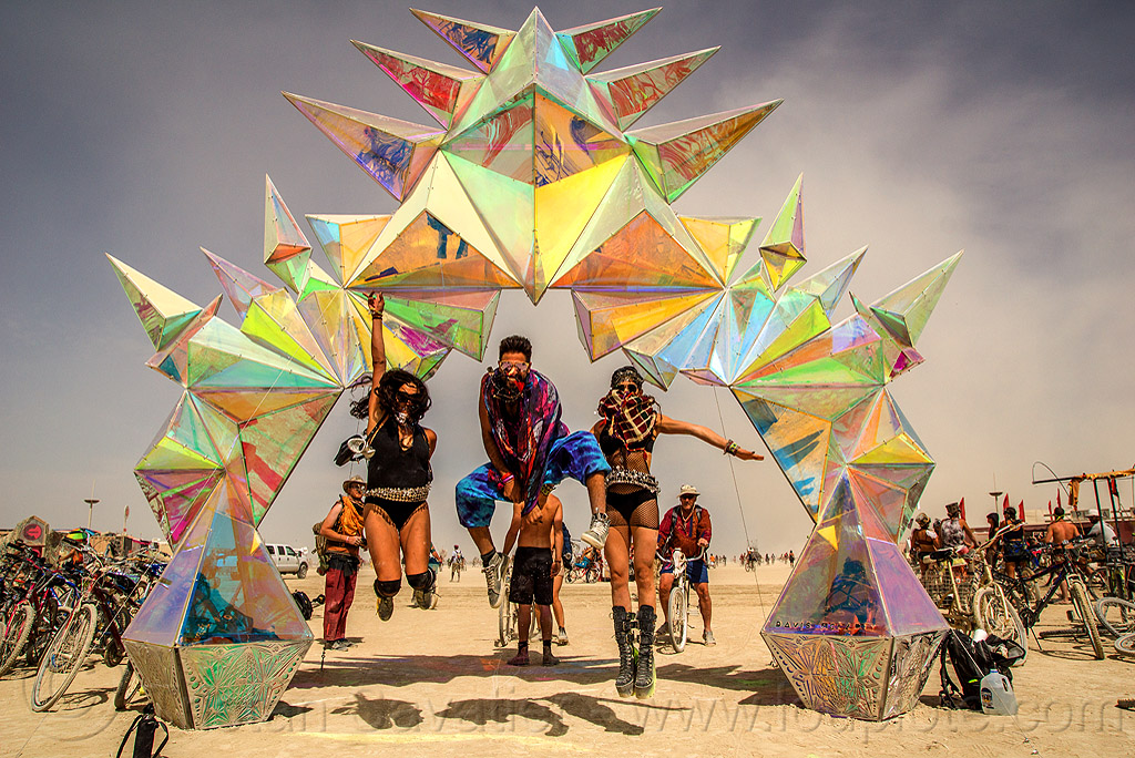 people jumping under the pulse portal - burning man 2016, arch, art installation, burning man, iridescent, pulse portal, sculpture