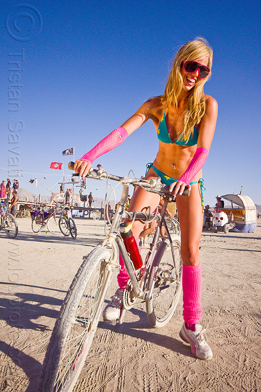 photo of blonde woman on bike with leg warmers - burning man 2012, bicycle, blonde, burning man, fashion, neon colors, standing, sunglasses, woman