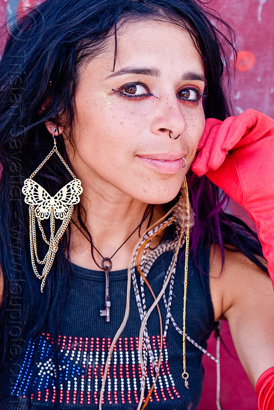 mumu and her butterfly earring, burning man, center camp, feather earring, flag, key necklace, nose piercing, people, puerto rican flag, puerto rico flag, septum piercing, woman