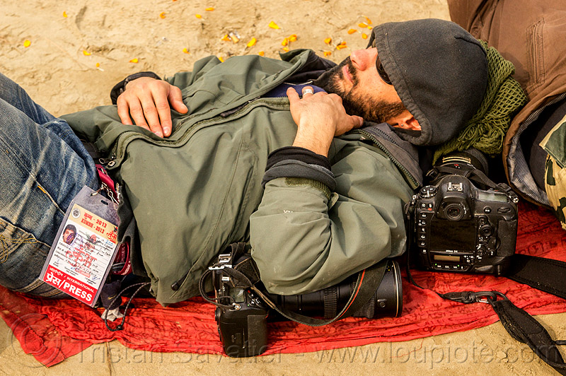 photographer jordano cipriani - kumbh mela 2013 festival (india), cameras, hindu, hinduism, jordano cipriani, kumbha mela, lying down, maha kumbh mela, man, napping, press pass, press photographer, resting, sleeping