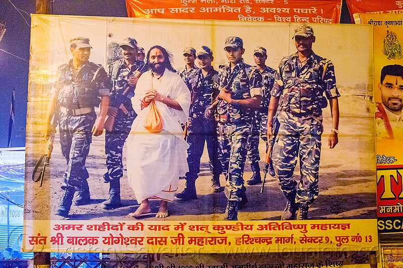 pilot baba with indian army soldiers - poster at kumbh mela 2013, fatigues, guru, hindu pilgrimage, hinduism, india, indian army, maha kumbh mela, men, military, night, pilot baba, poster, soldiers, uniform, walking, white robe