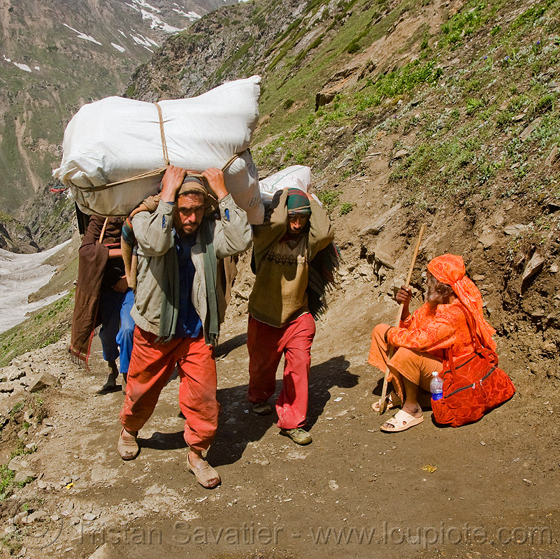 porters carrying heavy loads on trail - sadhu resting on trail - amarnath yatra (pilgrimage) - kashmir, amarnath yatra, baba, bags, bearers, hiking, hindu holy man, hindu pilgrimage, hinduism, india, kashmir, mountain trail, mountains, pilgrims, porters, resting, sadhu, trekking, wallahs