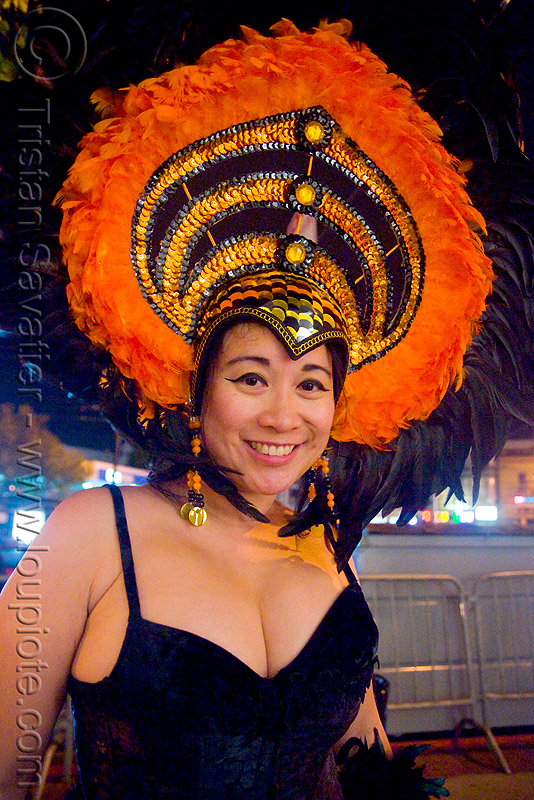 pretty asian woman in costume with large feather hat - halloween in the castro (san francisco), asian woman, cleavage, costume, feather hat, feathers, halloween, night, orange