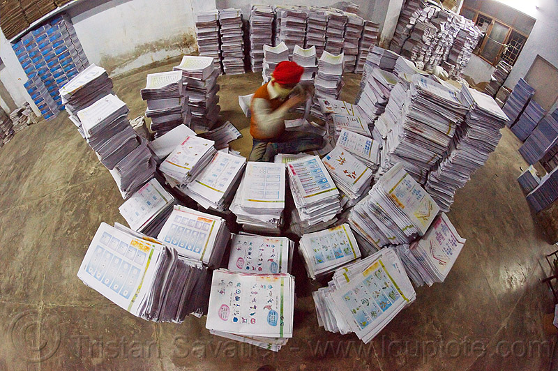 print shop worker collating leaflets into booklets, booklets, books, collating, fisheye, india, leaflets, lucknow, man, print shop, printed pages, printed paper, stacked, stacks, worker, working