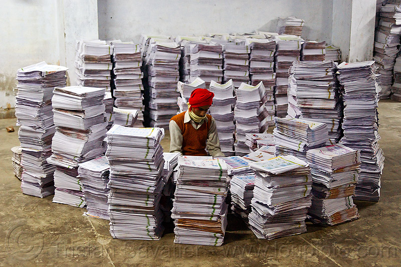 print shop worker collating printed pages into books, booklets, leaflets, lucknow, man, paper, people, printed paper, stacked, stacks, working
