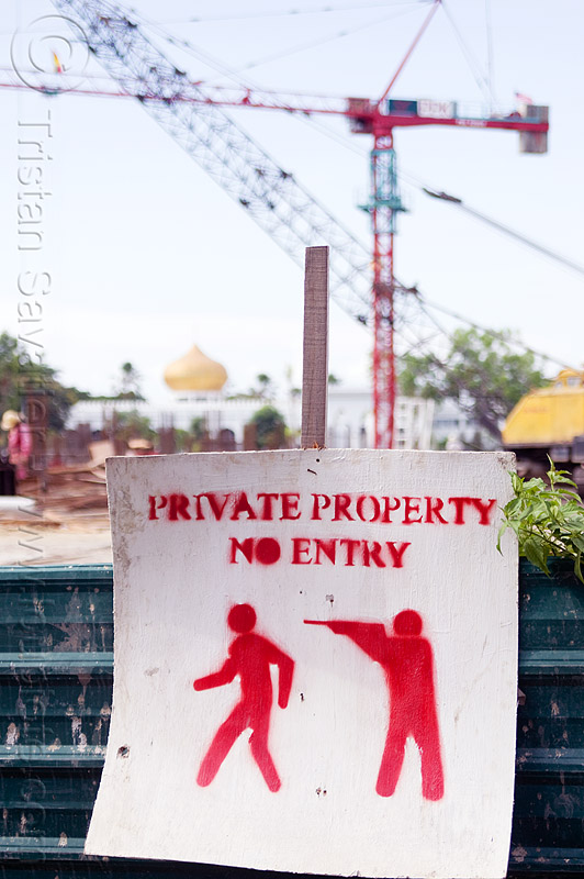 private property - no entry, armed guard, borneo, construction site, construction zone, cranes, gun, malaysia, no entry, no trespassing, private property, security guard, stencil, warning sign