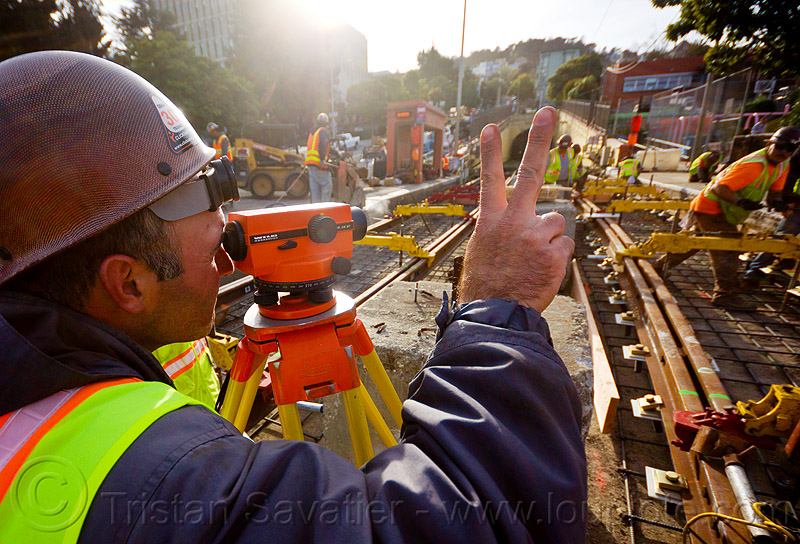 railroad construction survey - level, construction workers, duboce, geometer, high-visibility jacket, high-visibility vest, light rail, men, muni, ntk, railroad construction, railroad tracks, rails, railway tracks, reflective jacket, reflective vest, safety helmet, safety vest, san francisco municipal railway, survey level, surveyor, track maintenance, track work, tripod, working