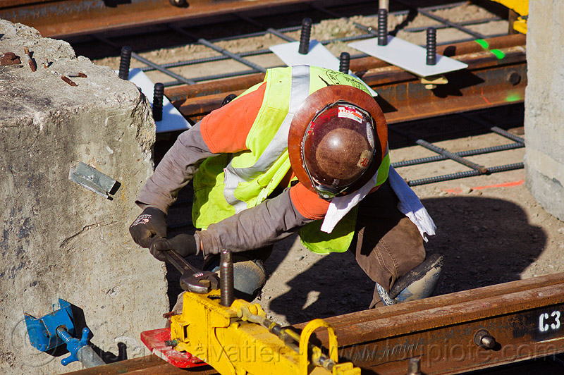 railroad construction worker adjusting a rail jack, construction worker, duboce, high-visibility jacket, high-visibility vest, light rail, men, muni, ntk, rail jacks, railroad construction, railroad tracks, rails, railway tracks, reflective jacket, reflective vest, safety helmet, safety vest, san francisco municipal railway, track jacks, track maintenance, track work, working, wrench