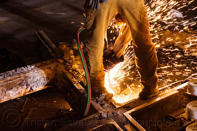 railroad worker cutting a track rail with a oxy-acetylene torch, high-visibility jacket, high-visibility vest, light rail, man, muni, night, ntk, oxy-acetylene cutting torch, oxy-fuel cutting, rail frog, railroad construction, railroad tracks, rails, railway tracks, reflective jacket, reflective vest, safety glasses, safety gloves, safety helmet, safety vest, san francisco municipal railway, sparks, track crossing, track maintenance, track work, welder, worker