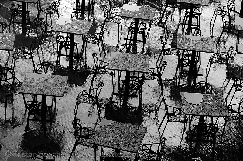 rain on black metal tables, chairs, water