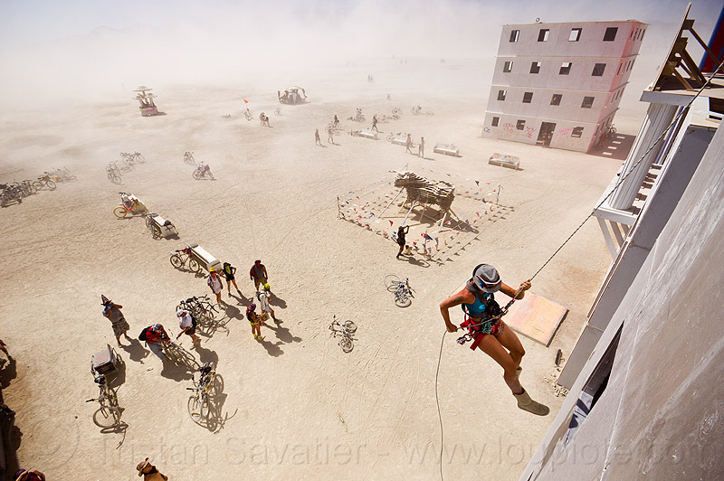 rappelling down wall street building - burning man 2012, abseiling, buildings, burning man, climbing harness, dust storm, haboob, hat, rappelling, rock climbing, single rope, static rope, vertical, wall street, white out, woman