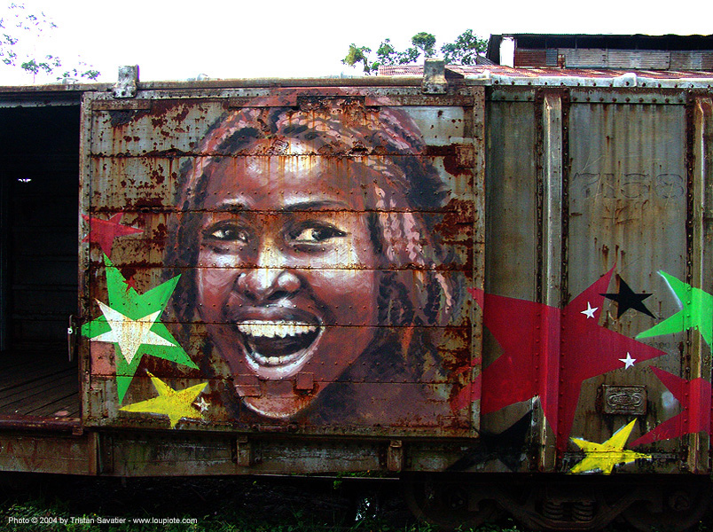 rasta-girl painting on train car - puerto limon (costa rica), abandoned, atlantic railway, costa rica, decay, freight train car, graffiti, mural, paint, painted, painting, puerto limon, rusted, rusty, stars, train depot, train yard, trespassing, urban exploration