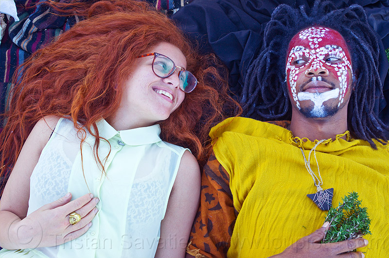 redhead woman - man with african tribal face paint, african american man, african face paint, black man, couple, curly hair, dolores park, dreads, eyeglasses, eyewear, face painting, facepaint, glasses, herbs, jason, long hair, lulu, lying down, makeup, necklace, people, red, spectacles, stone necklace, triangular necklace, tunic, white, yellow tunic
