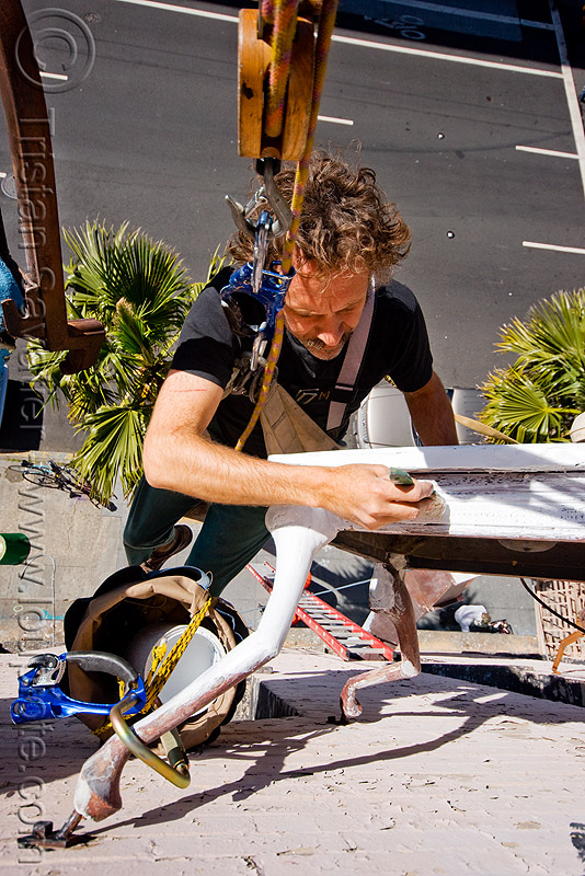 restoration of the defenestration building (san francisco), artist, brian goggin, hanging, harness, man, paint, painting, people, rope, rope access, ropework, safety harness, street, table, wall