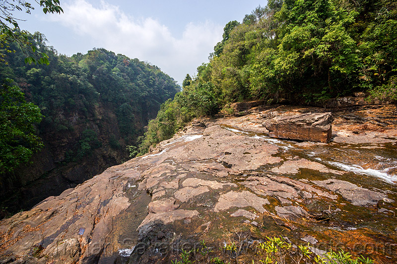 rocky river bed at top of large waterfall near mawlynnong (india), east khasi hills, jungle, mawlynnong waterfall, meghalaya, mountains, rain forest, river bed, rock, water