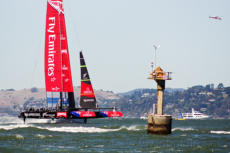 sailing hydrofoil catamaran emirates team new zealand near anita rock marker (san francisco bay), advertising, boat, fast, foiling, helicopter, hydrofoiling, ocean, racing, sailboat, sailing hydrofoils, sea, ship, speed, sponsors, water