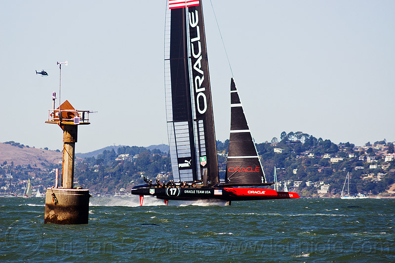sailing hydrofoil catamaran oracle team USA near anita rock marker (san francisco bay), ac72, advertising, america's cup, anita rock, bay, boat, catamaran, fast, foiling, hydrofoil catamarans, hydrofoiling, ocean, oracle team usa, race, racing, sailboat, sailing hydrofoils, sea, ship, speed, sponsors, water