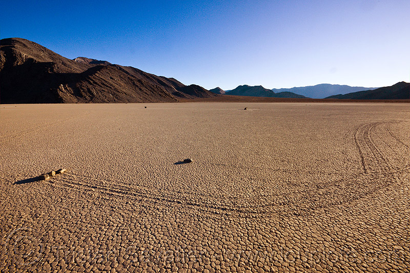 sailing stones travelling together on the racetrack - death valley, cracked mud, death valley, dry lake, dry mud, mountains, racetrack playa, sailing stones, sliding rocks