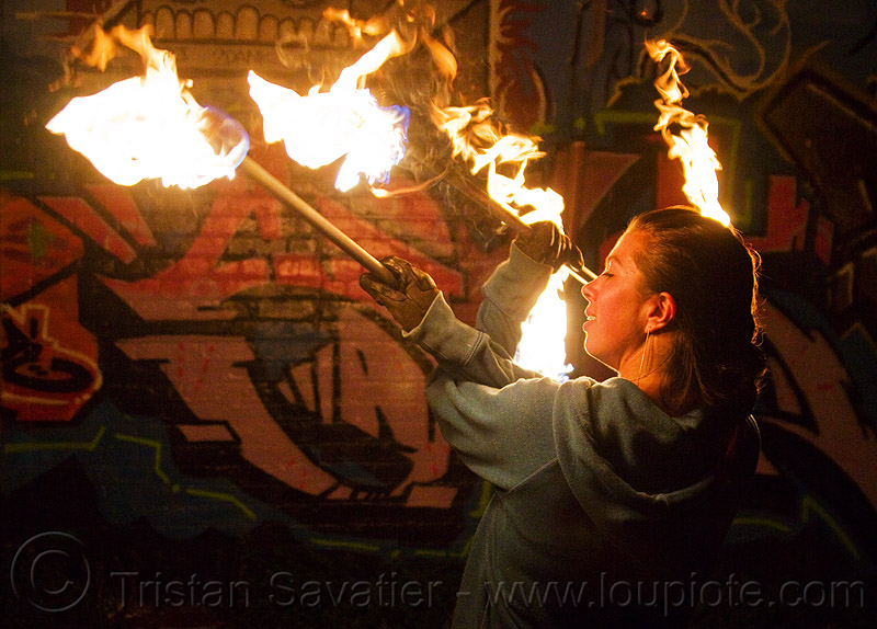 savanna spinning fire staffs, crossed arms, double staff, fire dancer, fire dancing, fire performer, fire spinning, fire staffs, fire staves, flames, graffiti, night, savanna, spinning fire, wall, woman